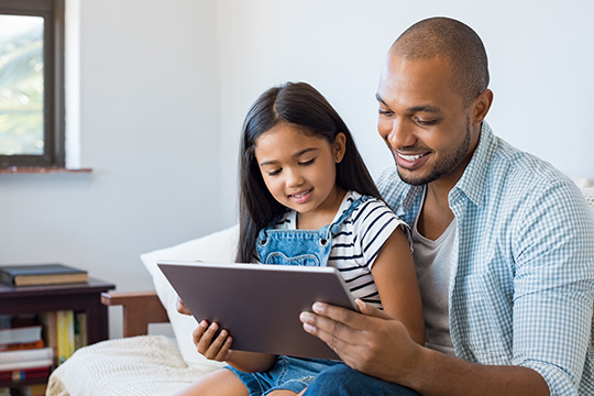 Young dad reading to his daughter on his tablet